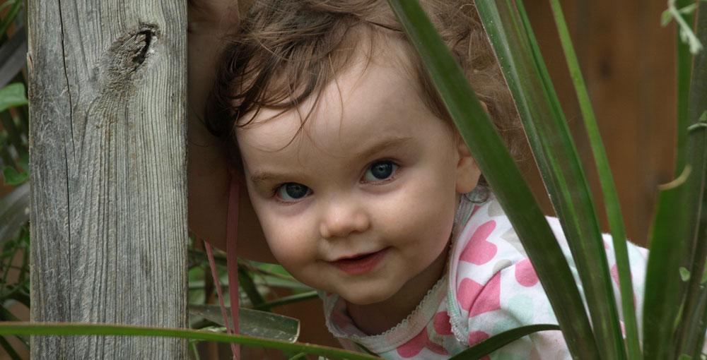 Child outdoors in plants