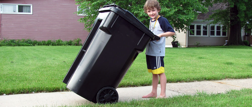 Image of a boy moving a garbage cart